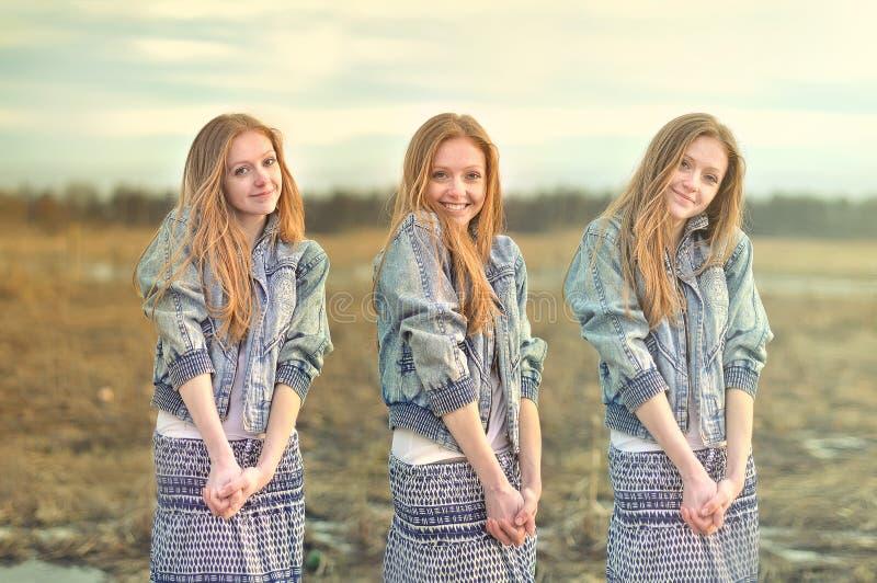 Nätt rödhårig flicka i bilden av tvilling- systrar arkivbild