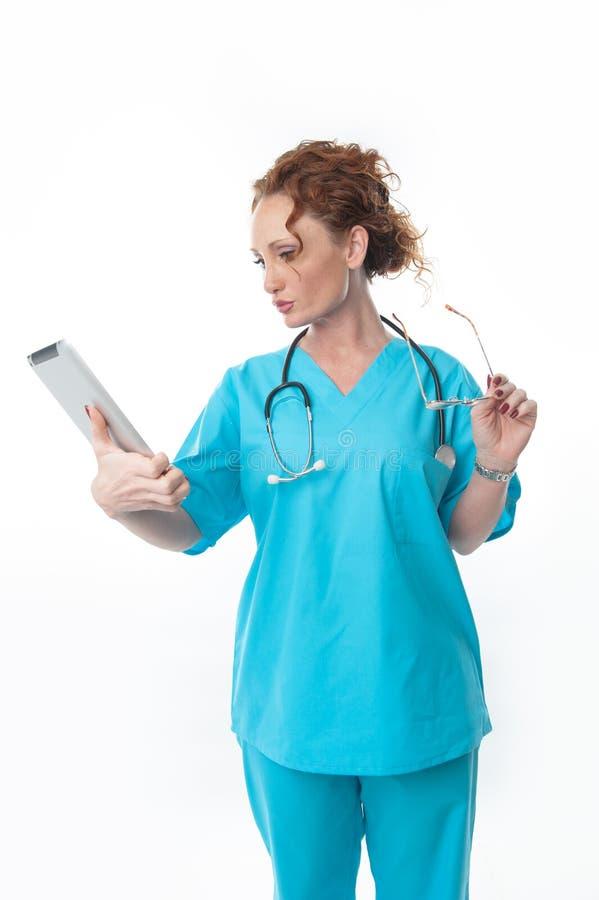Nätt rödhårig mankvinnasjuksköterska Looking på minnestavlan royaltyfri foto
