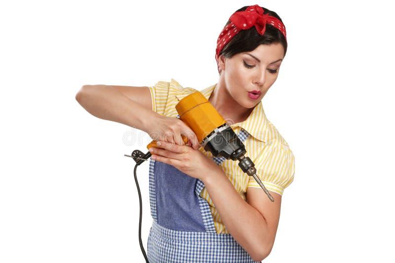 Nätt rolig flicka som kämpar med något hushållsarbete arkivfoto