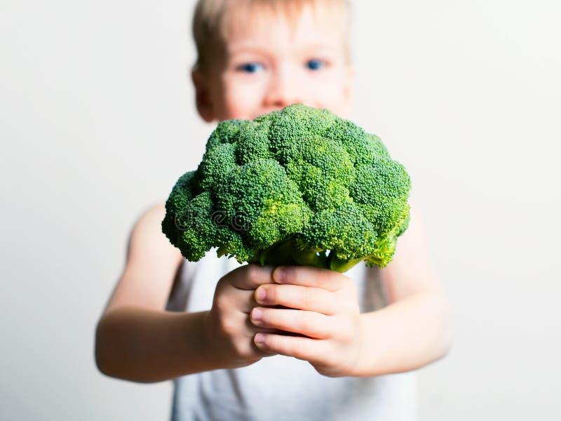 Nätt rolig pojke med broccoli Helthy och ren mat för barn royaltyfri foto