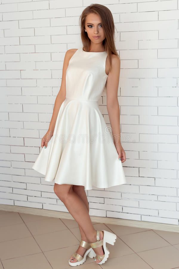 Nätt söt nätt flicka i en vit klänning i ljusa modeskor nära en tegelstenvägg i studion arkivfoto