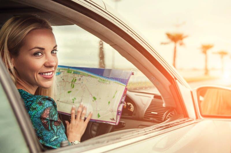 Nätt sammanträde för ung kvinna i bil med en vägöversikt royaltyfri bild