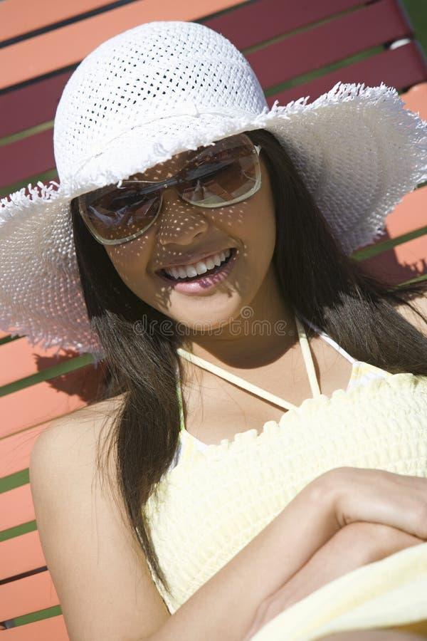 Nätt sammanträde för ung kvinna på solstol royaltyfri fotografi