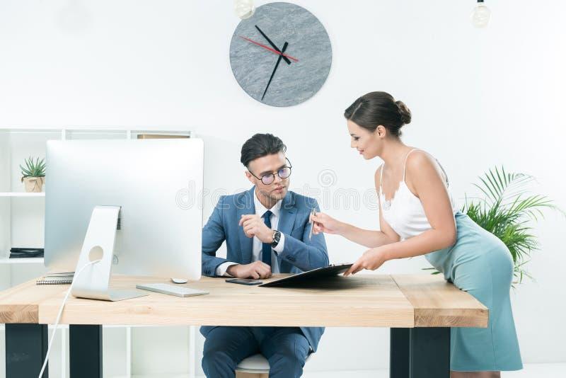 Nätt sekreterare som talar till hennes framstickande på kontoret arkivbilder