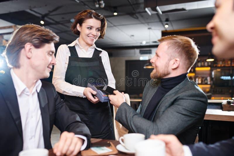 Nätt servitris som ger terminalen för betalning till affärsmannen fotografering för bildbyråer