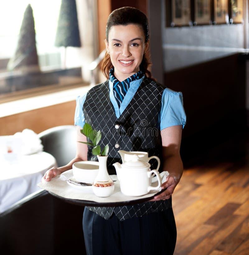 Nätt servitris som poserar med tea för gäster arkivfoton