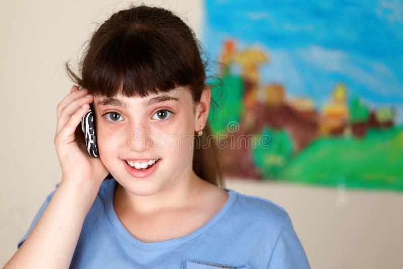 Nätt skolaflicka som använder mobilen royaltyfri bild