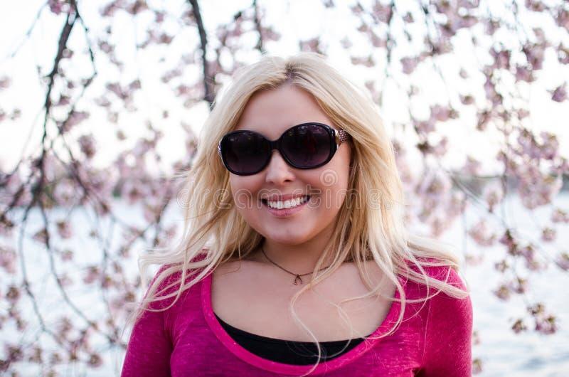 Nätt skymningsolnedgångstående av en blond kvinna som poserar vid Cherry Blossom blommor arkivbilder