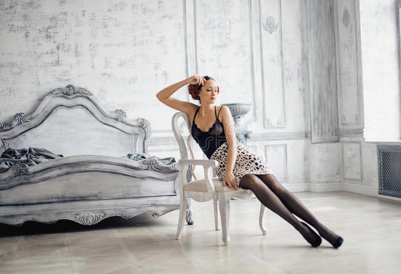 Nätt slank brunettkvinna som vilar i lyxigt rum arkivbild