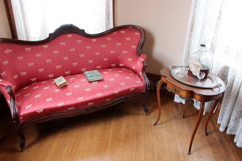 Nätt soffa- och trätabell med böcker och drinken inom det historiska museet för 1890 hus, Cortland, New York, 2018, royaltyfria foton