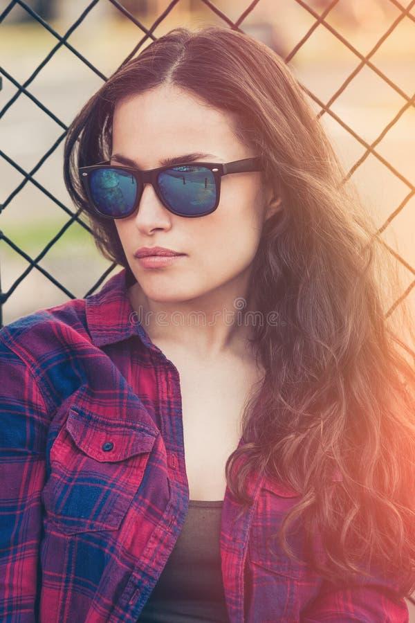 Nätt stads- stående för ung kvinna med solglasögon arkivfoto