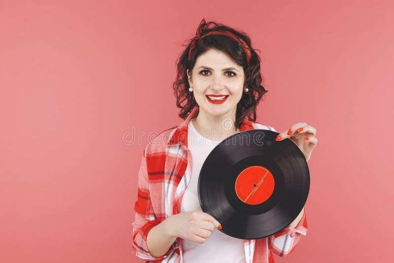Nätt stift upp kvinna med vinyl som isoleras över thered backgruond arkivfoto
