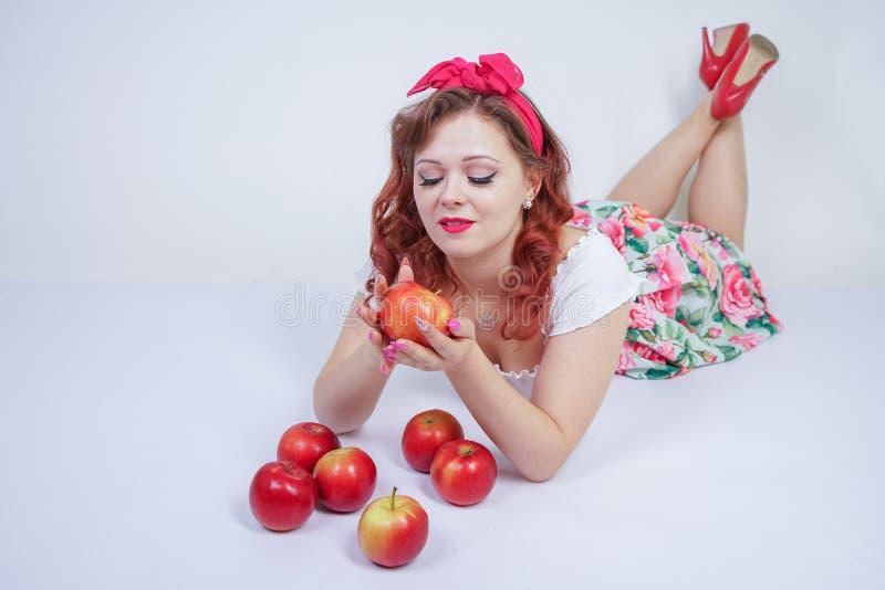 Nätt stift upp lyckligt posera för caucasian ung flicka med röda äpplen gullig tappningdam i den retro klänningen som har gyckel  royaltyfria bilder