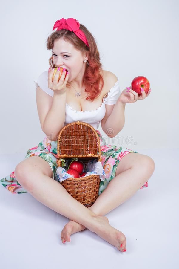 Nätt stift upp lyckligt posera för caucasian ung flicka med röda äpplen gullig tappningdam i den retro klänningen som har gyckel  arkivbilder