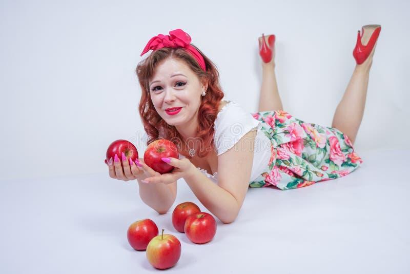 Nätt stift upp lyckligt posera för caucasian ung flicka med röda äpplen gullig tappningdam i den retro klänningen som har gyckel  arkivbild