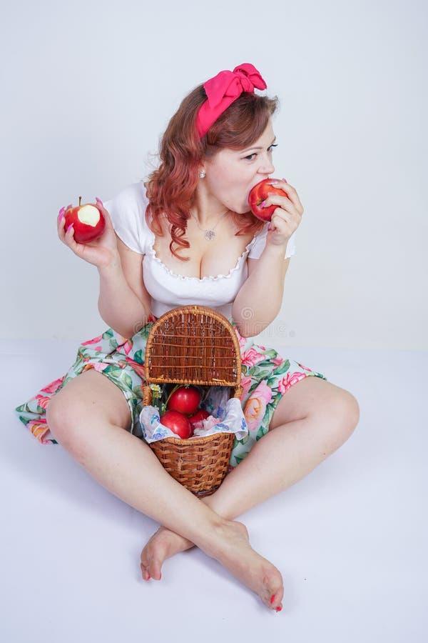Nätt stift upp lyckligt posera för caucasian ung flicka med röda äpplen gullig tappningdam i den retro klänningen som har gyckel  arkivfoto