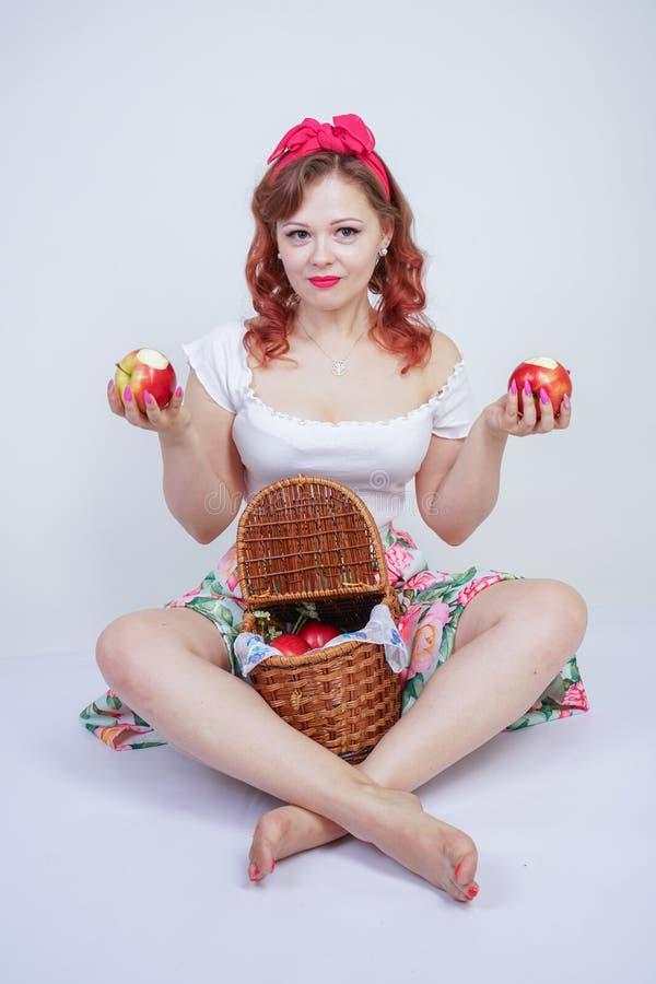 Nätt stift upp lyckligt posera för caucasian ung flicka med röda äpplen gullig tappningdam i den retro klänningen som har gyckel  arkivfoton