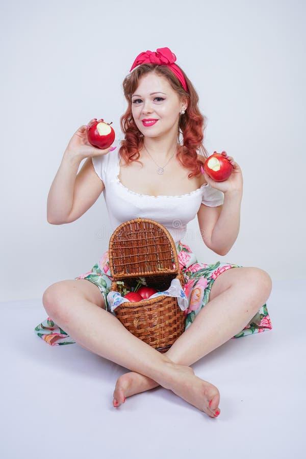 Nätt stift upp lyckligt posera för caucasian ung flicka med röda äpplen gullig tappningdam i den retro klänningen som har gyckel  royaltyfri foto
