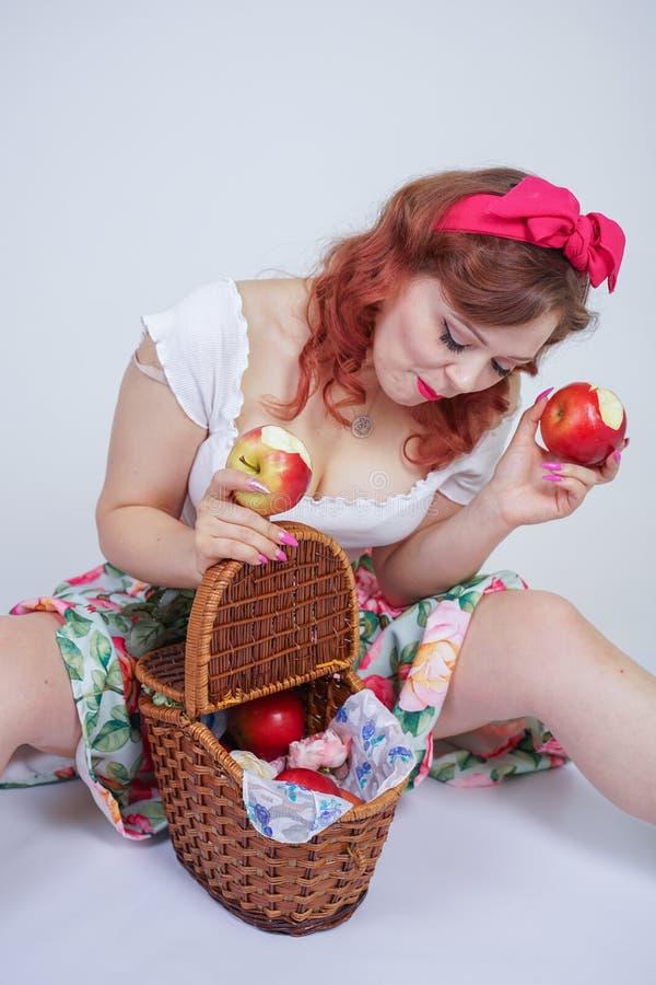 Nätt stift upp lyckligt posera för caucasian ung flicka med röda äpplen gullig tappningdam i den retro klänningen som har gyckel  fotografering för bildbyråer