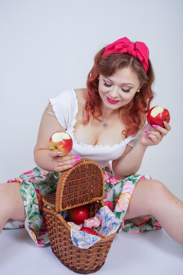 Nätt stift upp lyckligt posera för caucasian ung flicka med röda äpplen gullig tappningdam i den retro klänningen som har gyckel  royaltyfri fotografi