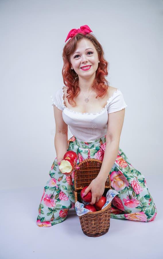 Nätt stift upp lyckligt posera för caucasian ung flicka med röda äpplen gullig tappningdam i den retro klänningen som har gyckel  royaltyfri bild
