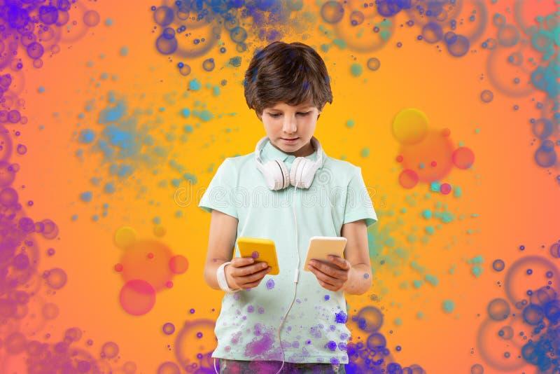 Nätt stilig pojke som granskar massager på telefoner arkivfoto
