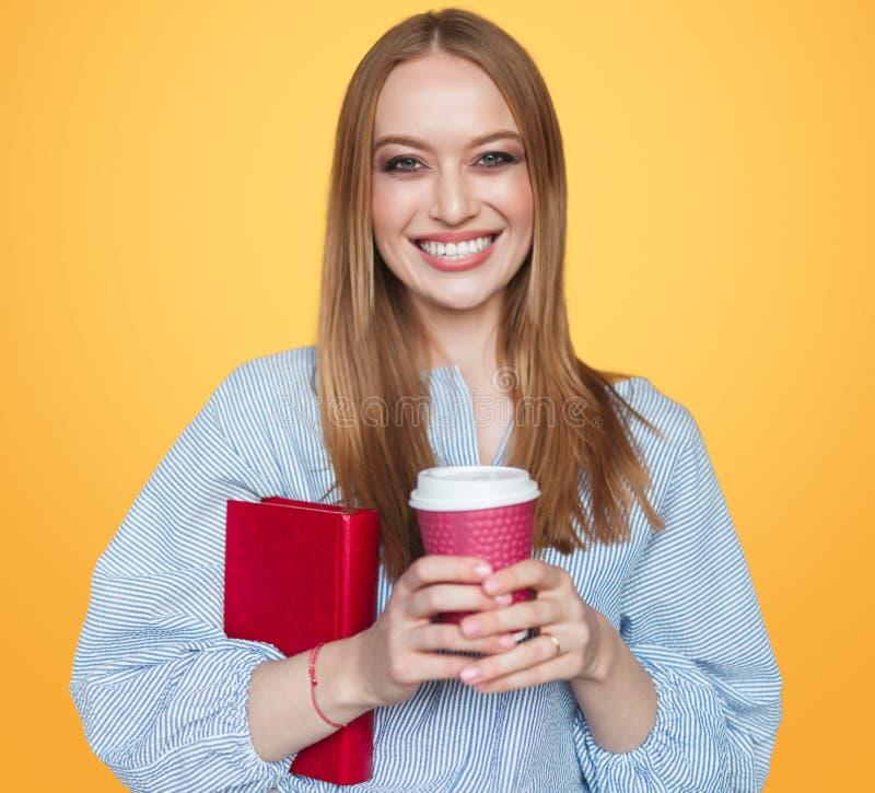 Nätt student med kaffe och boken arkivbild