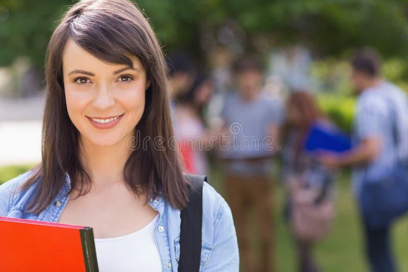 Nätt student som ler på kameran utanför på universitetsområde arkivbilder