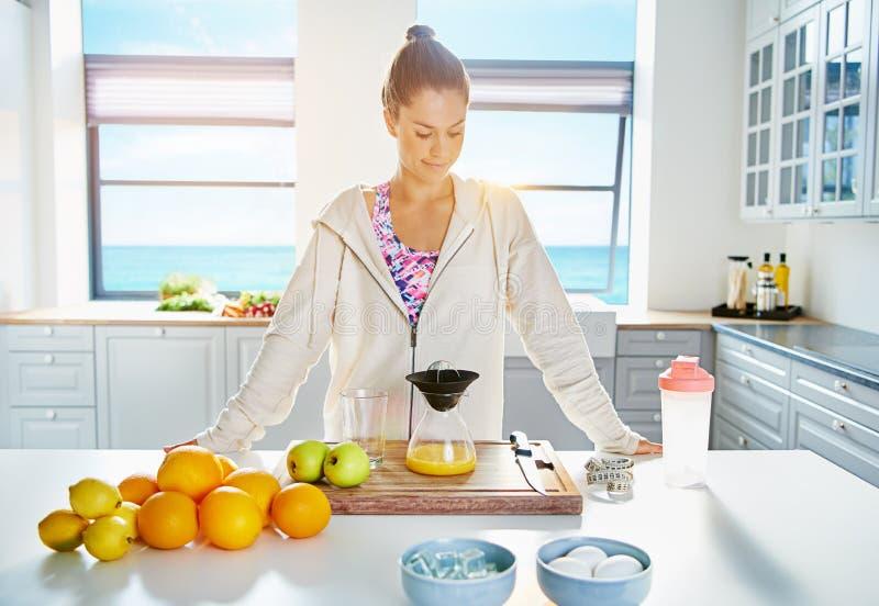 Nätt sund ung kvinna som gör ny fruktsaft arkivfoton