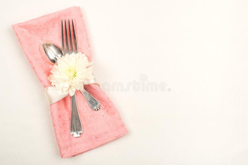 Nätt tabellinställning med den Peachy rosa torkdukeservetten med gaffeln, skeden och den vita krysantemumblomman på den av vita b fotografering för bildbyråer