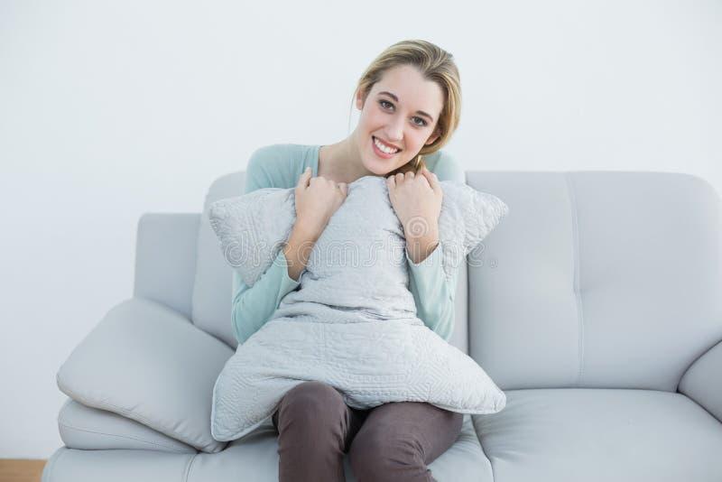 Nätt tillfälligt kvinnasammanträde på soffainnehavet som ler en kudde royaltyfria bilder