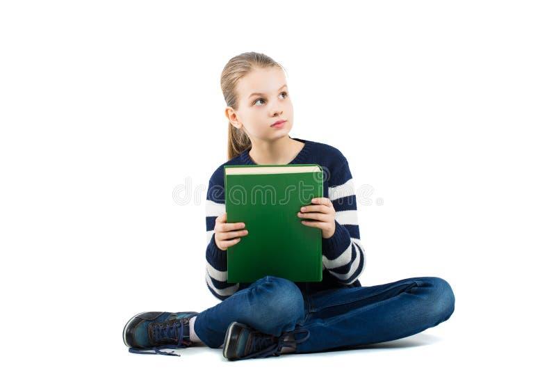 Nätt tonårigt flickasammanträde på golvet med en bok i hans händer arkivbild