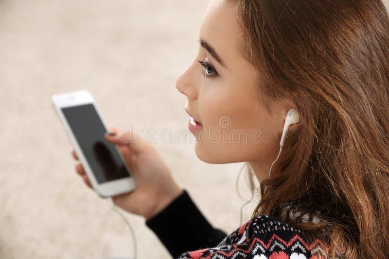 Nätt tonåringflicka med telefonsammanträde i rum royaltyfria bilder