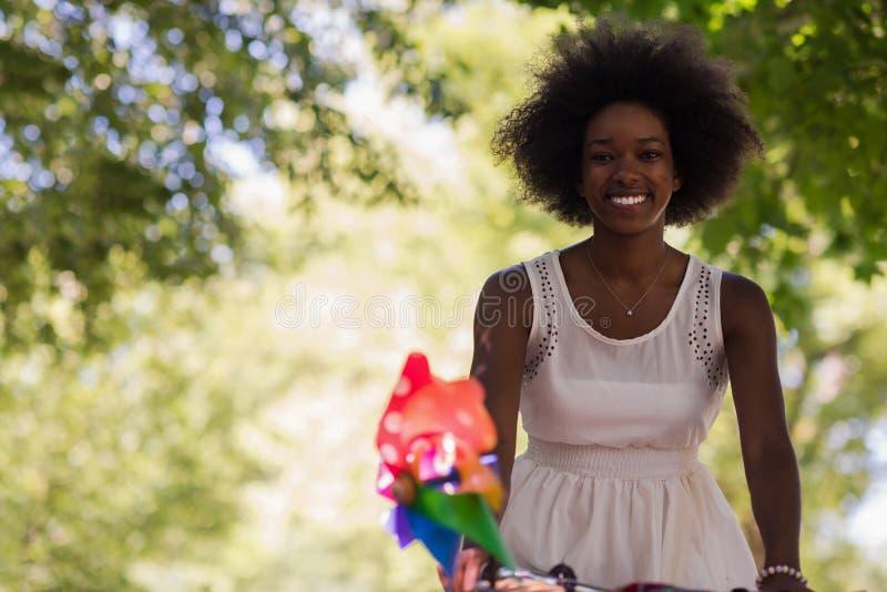 Nätt ung afrikansk amerikankvinna som rider en cykel i skog arkivfoto