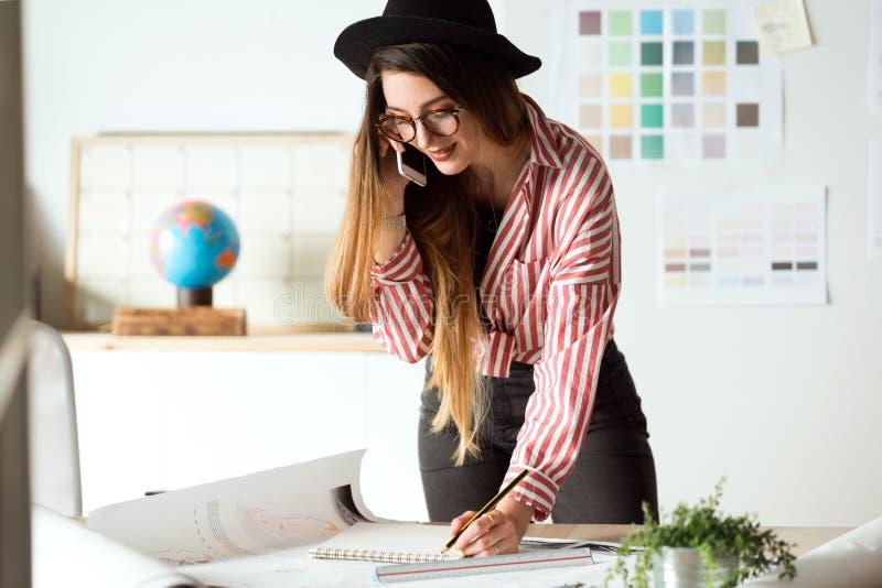Nätt ung arkitektkvinna som arbetar på ritningar, medan tala på telefonen i kontoret royaltyfri fotografi