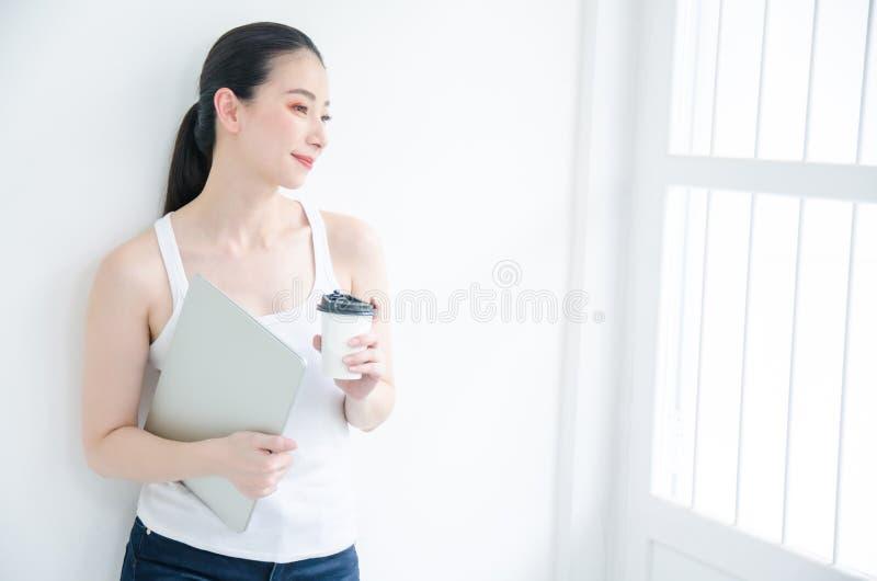 Nätt ung asiatisk affärskvinna som rymmer en kopp kaffe och dokumentmappar Isolerad studiostående som ler på vit bakgrund arkivfoton