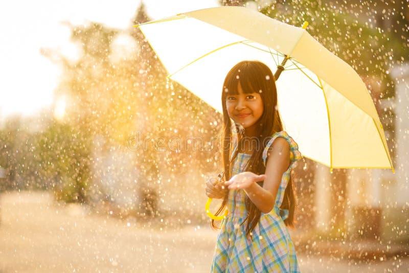 Nätt ung asiatisk flicka i regnet royaltyfri bild