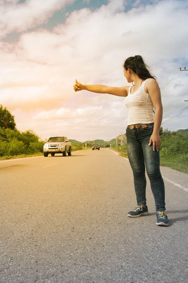 Nätt ung asiatisk kvinna med handen som kallar upp den övergående bilen fotografering för bildbyråer
