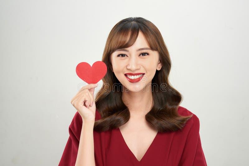 Nätt ung asiatisk kvinna som rymmer vitbokhjärta och lyckligt ler på kameran arkivfoto