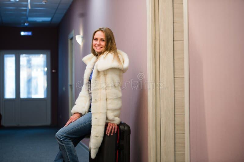 Nätt ung blond kvinnaresande som bär ett lag, jeans som drar ett dräktfall royaltyfri bild
