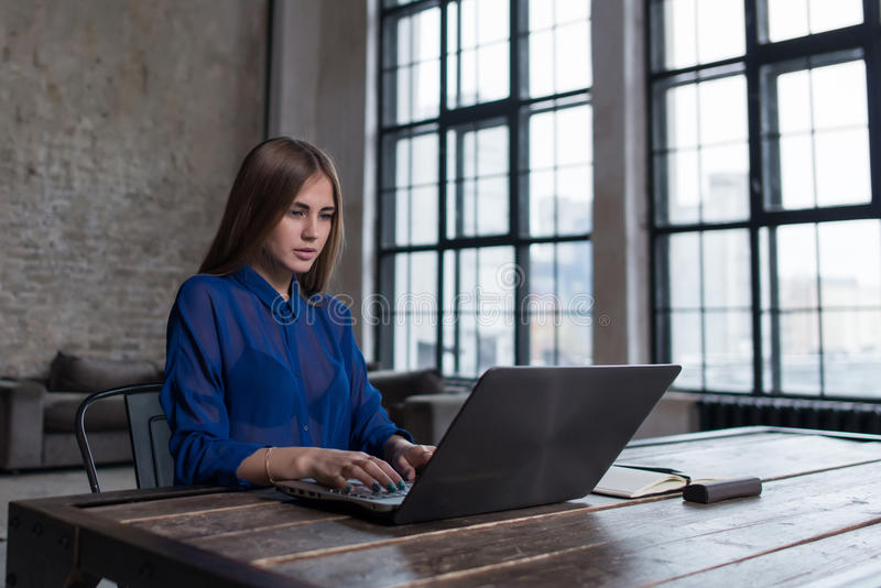 Nätt ung brunett som arbetar på bärbara datorn på trätabellen i rymlig mörk vindstudio fotografering för bildbyråer