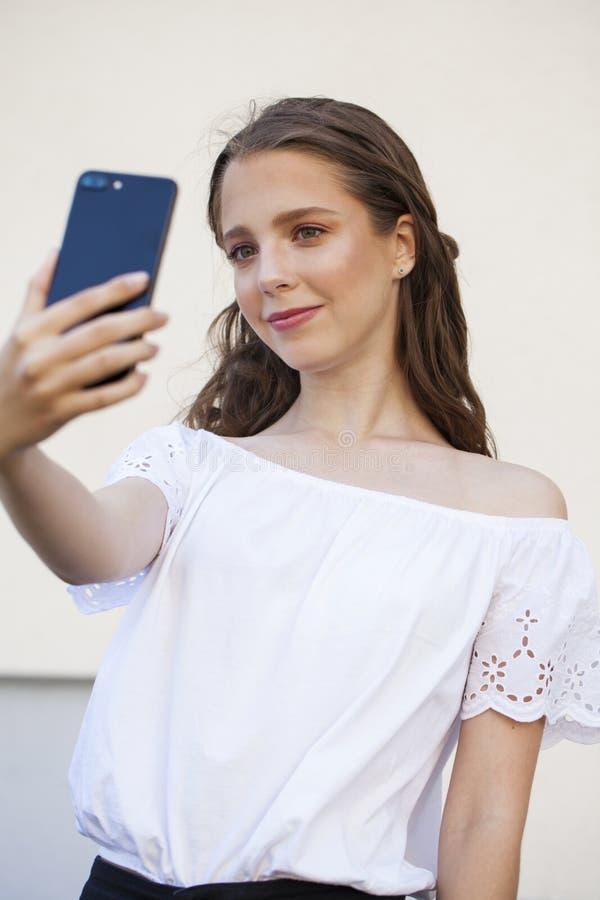Nätt ung brunettkvinna som gör selfie på smartphonen arkivfoton