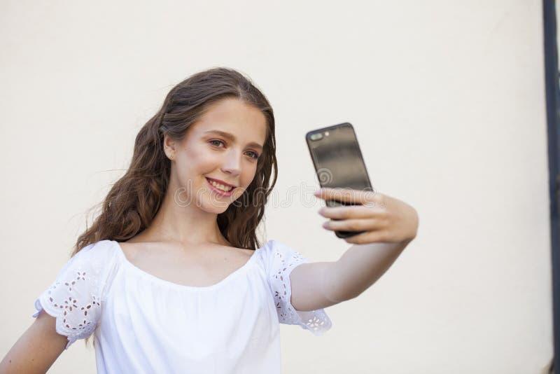 Nätt ung brunettkvinna som gör selfie på smartphonen royaltyfri foto