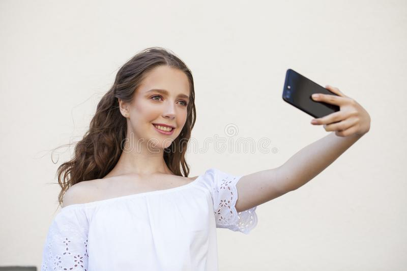 Nätt ung brunettkvinna som gör selfie på smartphonen royaltyfria bilder