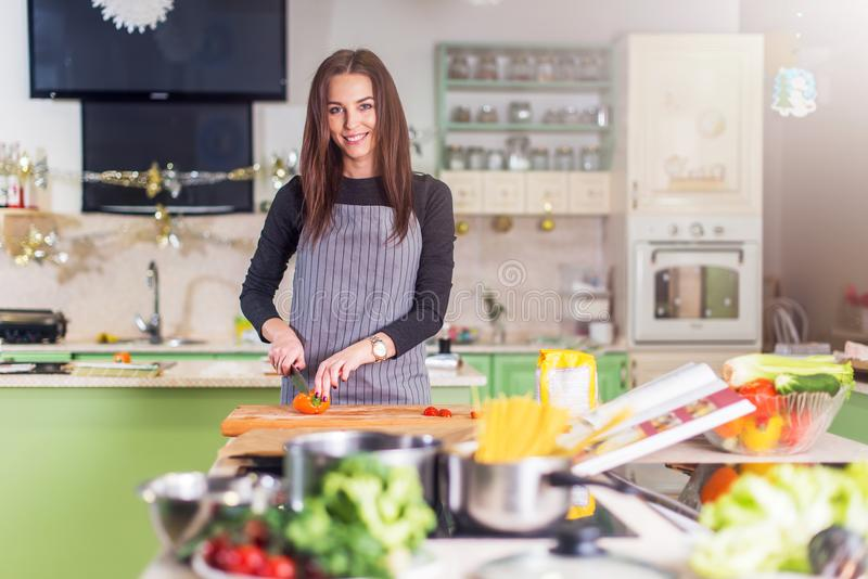 Nätt ung Caucasian kvinnadanandepizza av receptboken som framlänges hugger av grönsaker på skärbräda i henne royaltyfri fotografi