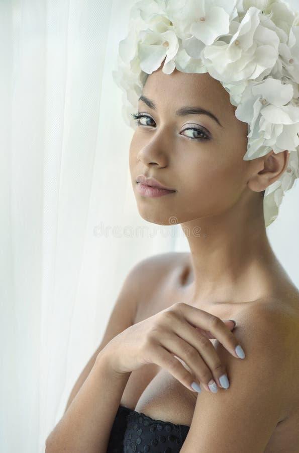 Nätt ung dam med en blommahatt royaltyfri fotografi