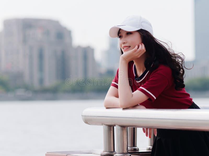 Nätt ung flicka för mode med svart långt hår, den bärande röda T-tröja och den vita baseballmössan som poserar utomhus- minimalis arkivbild