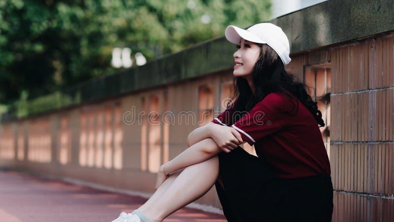 Nätt ung flicka för mode med svart långt hår, den bärande röda T-tröja och den vita baseballmössan som poserar utomhus- minimalis arkivfoton