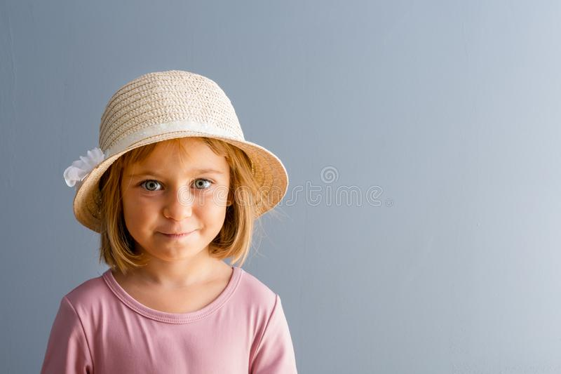 Nätt ung flicka i sugrörhatt och rosa skjorta arkivfoto