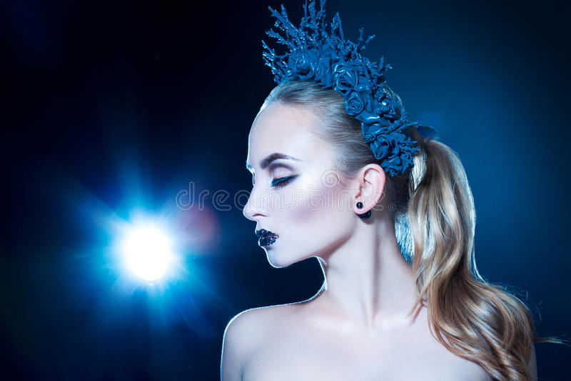 Nätt ung flicka med kransen på head och trevlig makeup på svart arkivfoto